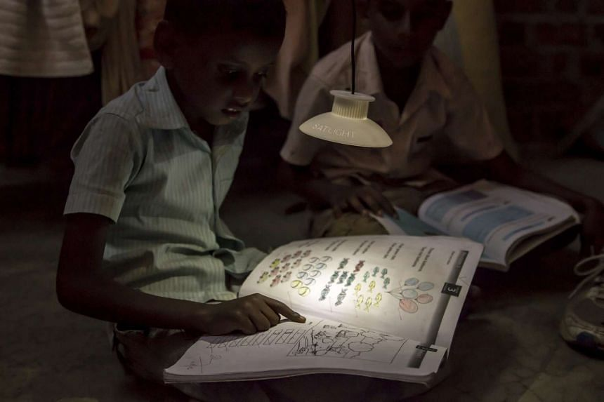 A boy reading under the SatLight attachment of GravityLight, charged by hanging weights from a small generator.