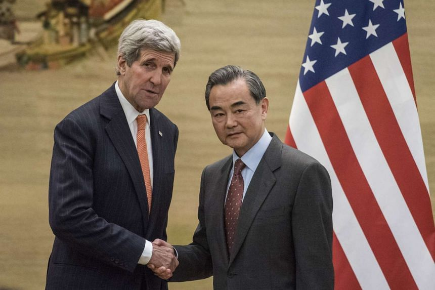 Chinese Foreign Minister Wang Yi (right) shaking hands with US Secretary of State John Kerry at the end of a press conference in Beijing on Jan 27, 2016.