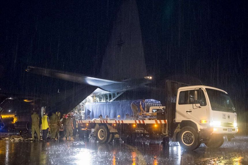 Aid supplies including ration packs and water containers are unloaded from a Royal New Zealand Air Force aircraft after Cyclone Winston in Fiji.