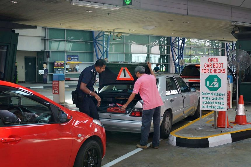 A police officer conducting a routine check on a car at Woodlands Checkpoint.