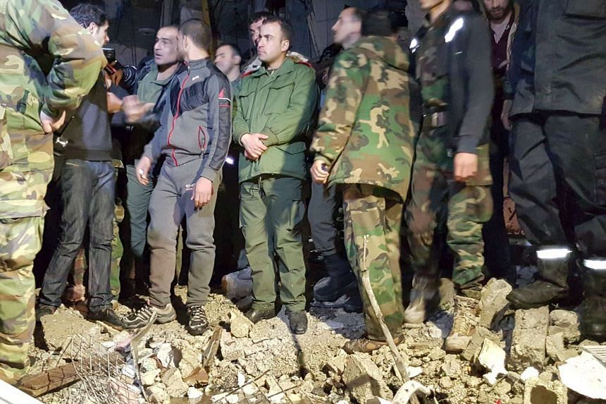 Syrian army soldiers and civilians inspect the site of multiple bomb blasts that hit the Sayeda Zeinab area, a southern district of Damascus on Sunday (Feb21).