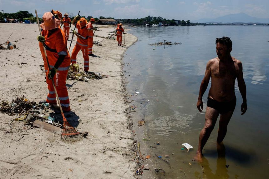 City cleaners collect floated debris on a beach at Guanabara bay in Rio de Janeiro, Brazil on Dec 26, 2015. The bay, where the nautical sports of Rio 2016 Olympic Games will take place, receives sewage directly from the city system.