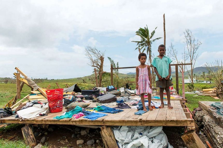 Children standing amongst the ruins of a house in the Rakiraki district of Fiji after Cyclone Winston swept through the area.