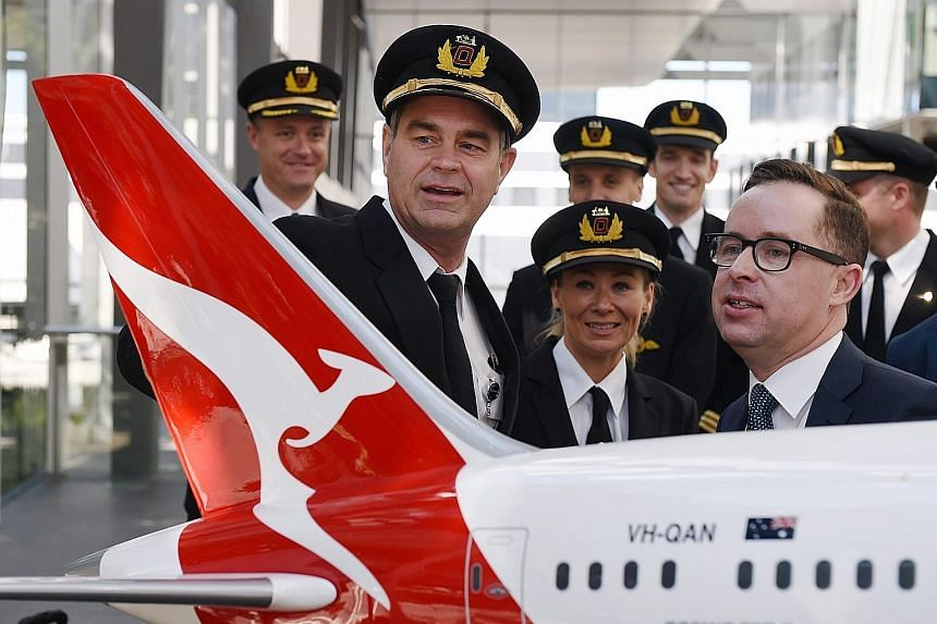 Qantas CEO Alan Joyce (right in photo) chatting with pilots after announcing the airlines' first-half net profit of 234 per cent at a media briefing in Sydney, Australia, yesterday.