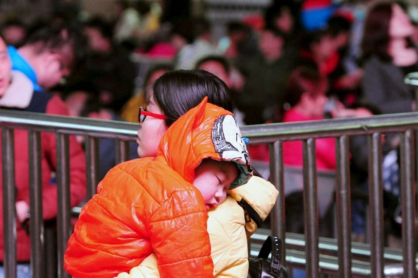 A woman carries a child as passengers wait to board a train during the Chinese Lunar New Year travel rush at a railway station in Jiujiang, Jiangxi province, Feb 13, 2016.