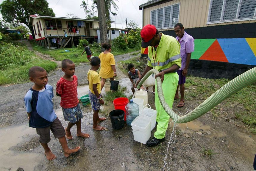 A worker from Suva's City Council fills residents' buckets with fresh water after power outages caused by Cyclone Winston stopped pumps from working.