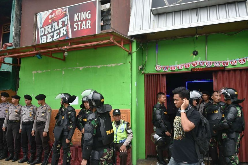Indonesian police and military personnel stand watch outside a cafe during a raid at the Kalijodo red-light district in Jakarta.