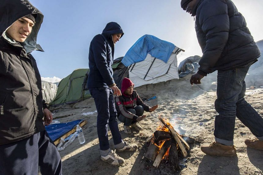 "Migrants warm their hands in the makeshift camp called the ""Jungle"" in Calais, France, Feb 15, 2016."