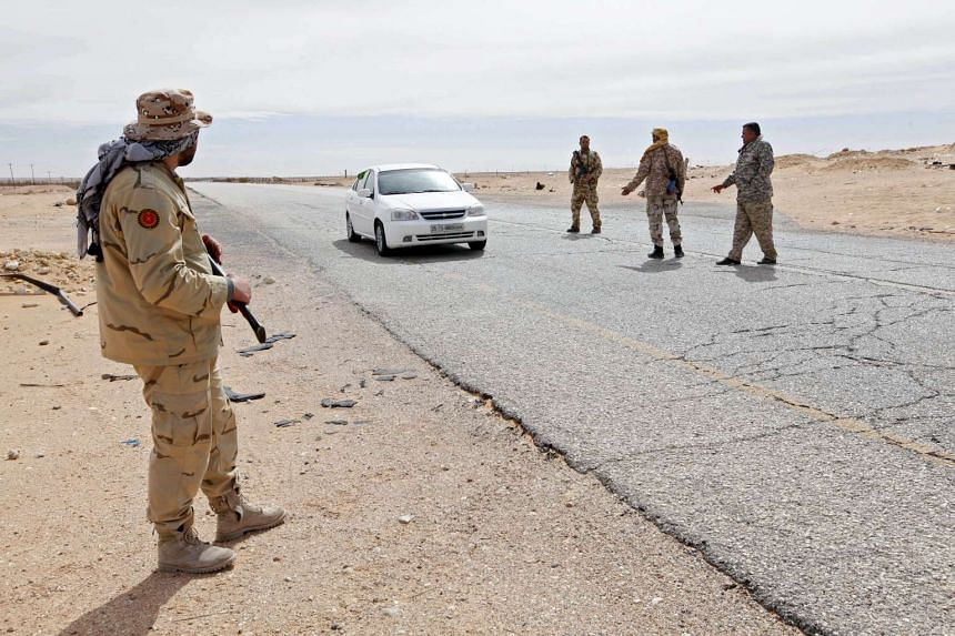 Libyan soldiers manning a military outpost stop a car at a checkpoint in Libya.