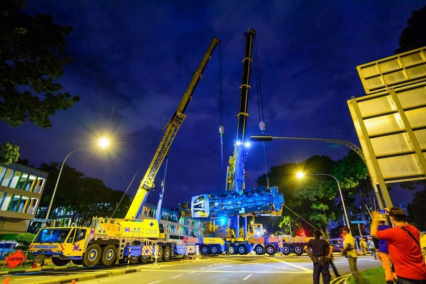 The fallen crane being loaded onto a trailer.
