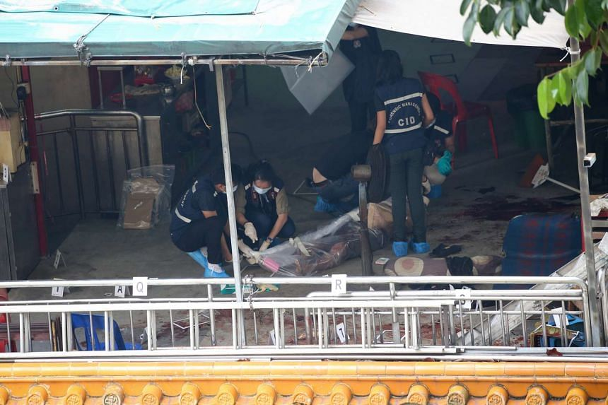 Police officers inspecting the scene where Mr Tan Poh Huat's body was found in the temple.