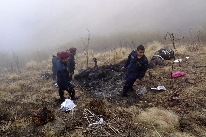 Nepalese police officers searching for victims at the crash site of the Tara airlines plane crash, in Dana village, in Nepal's Myagdi district, on Feb 24, 2016.