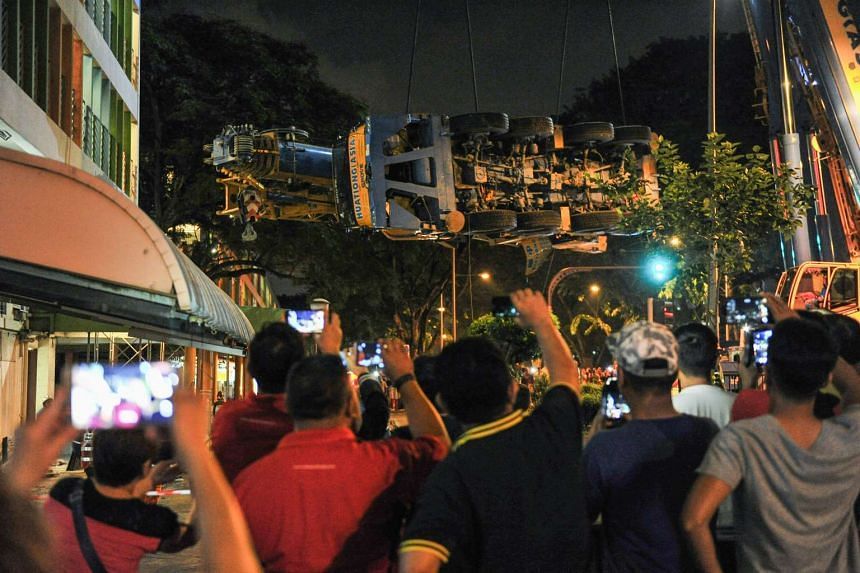 The public taking photos of the mobile crane being hoisted into the air at 2.30am.