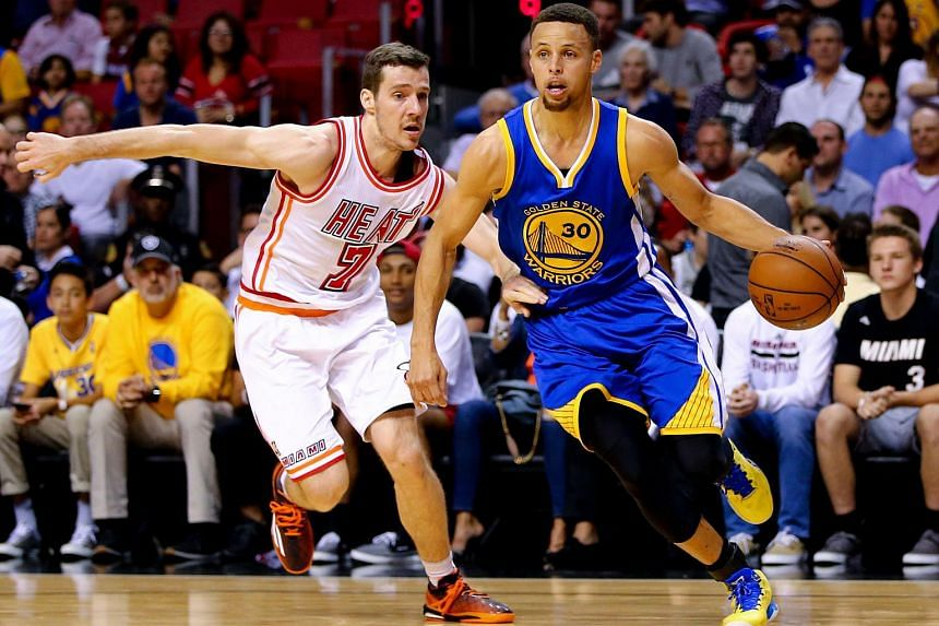 Stephen Curry (right) of the Golden State Warriors drives past Goran Dragic of the Miami Heat at the American Airlines Arena on Feb 24.