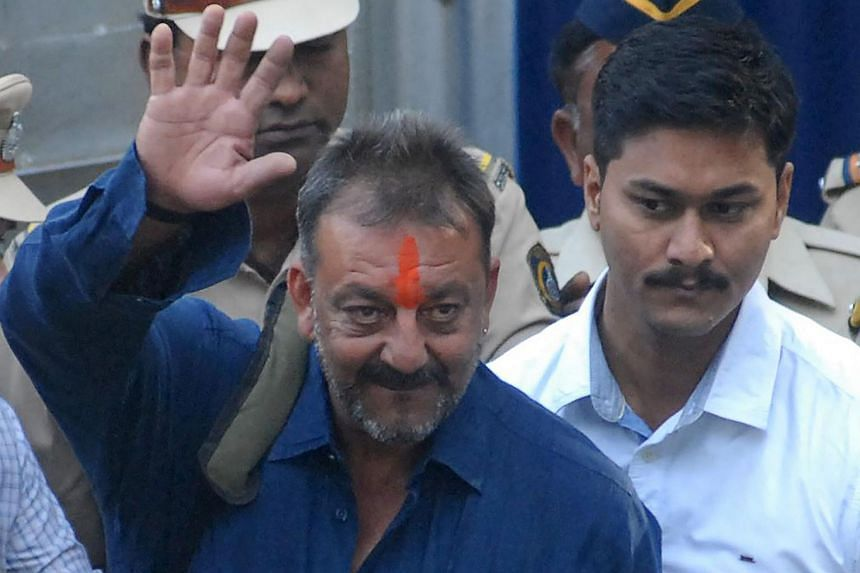 Indian Bollywood actor Sanjay Dutt (centre) waves as he is escorted by officials from Yerwada Jail in Pune, on Feb 25, 2016.