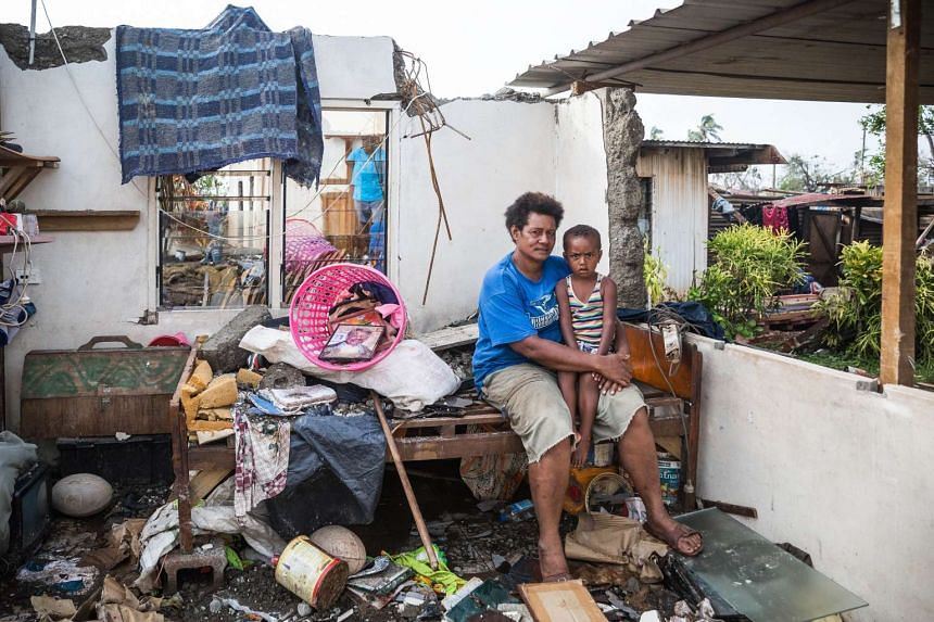 A woman holding her son in the remnants of her house after Cyclone Winston devastated Fiji.