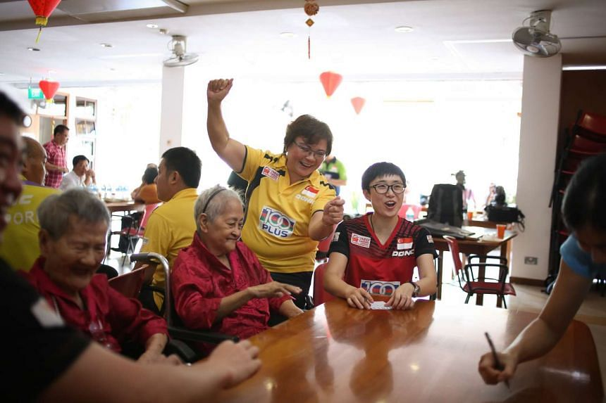 STTA president Ellen Lee (centre) and Singapore paddler Feng Tianwei (right) playing bingo with elderly residents at Man Fut Tong nursing home on Feb 25, 2016.
