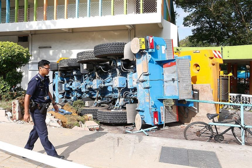 The mobile crane crash (above and left) yesterday morning left a roughly 2m-wide hole in the wall of the POSB bank branch on the ground floor of Block 2A in Woodlands Town Centre. Eyewitnesses said that the driver of the crane escaped unhurt with the