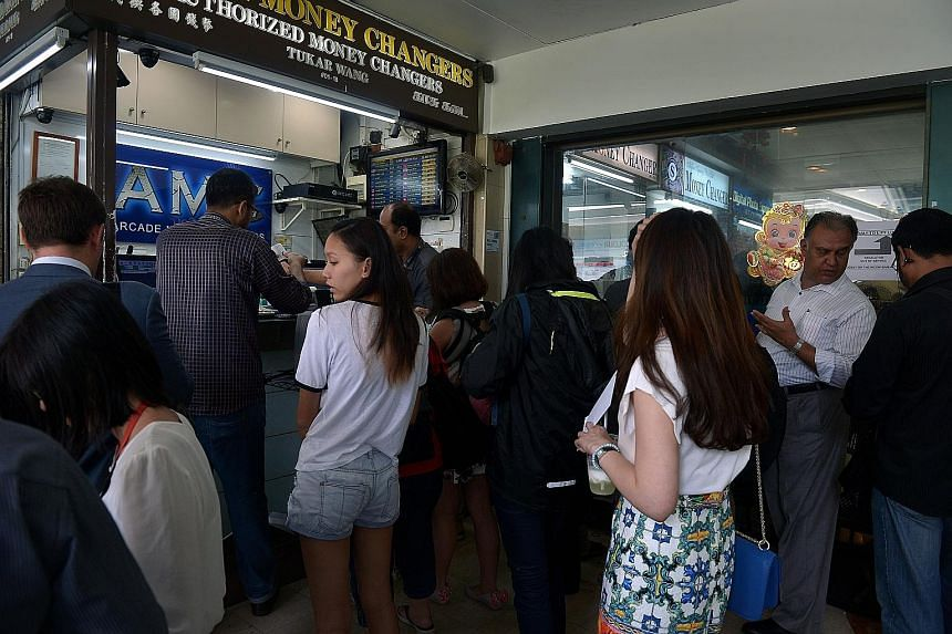 Customers queueing at a money changer in Raffles Place on Tuesday. Britain's pound slid for a third day yesterday, touching 1.9568 Singdollars, its lowest level since June 2013.