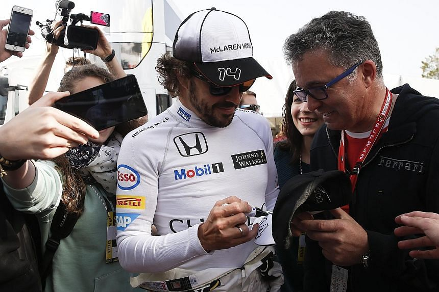McLaren driver Fernando Alonso signs autographs in Barcelona (above) after completing laps in his improved MP4-31 car (left) during the testing session. Drivers will have to get used to the new rules for qualifying, as part of a range of measures to