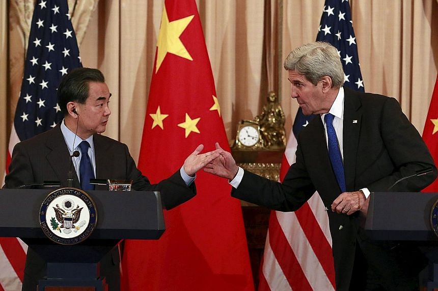 Chinese Foreign Minister Wang Yi (left) and US Secretary of State John Kerry at a joint press conference after their meeting in Washington on Tuesday. While neither budged on the South China Sea issue, both officials indicated that they were near agr