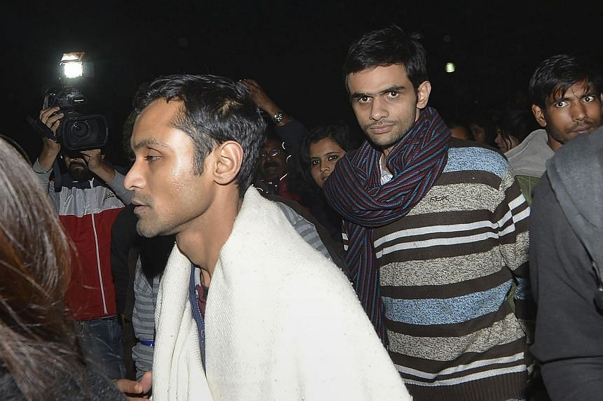 Indian student activists Umar Khalid (with striped scarf) and Anirban Bhattacharya (with white shawl) walking across the campus of New Delhi's Jawaharlal Nehru University on their way to surrendering to the Indian authorities on Tuesday.