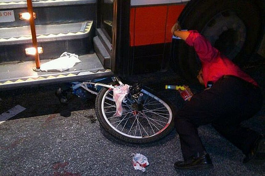 A handout picture taken by the victim's aunt showing the boy's bicycle pinned under the bus. He was riding across the zebra crossing on Choa Chu Kang North 5 when he was knocked down by an SMRT bus and dragged for about 10m. His left foot, which was