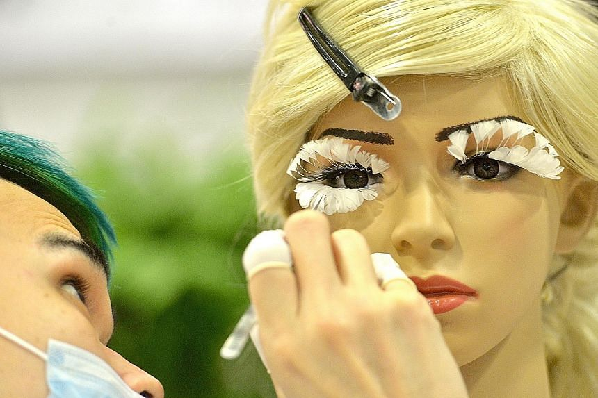 Eyelash master Andy Tiang Zhi Pink, 23, from Andy Chang Beauty Station in Kuala Lumpur, putting feather eyelashes on a mannequin at the BeautyAsia 2016 trade exhibition at Suntec Singapore yesterday. Mr Tiang won the first prize in the Artistic Eyela