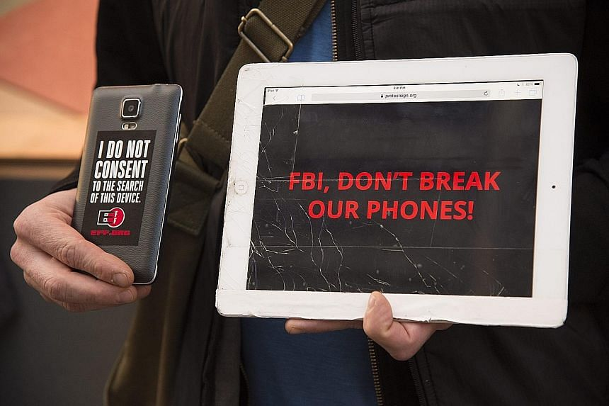 """A protest in front of an Apple Store in San Francisco on Tuesday. Apple says law enforcement agencies nationwide """"have hundreds of iPhones they want Apple to unlock"""" if the FBI wins the San Bernardino case."""