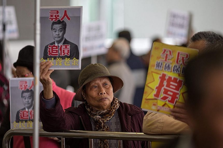 Protesters demanding universal pensions outside the Legislative Council before the annual budget announcement in Hong Kong yesterday. Financial Secretary John Tsang expects Hong Kong's economy to grow just 1 per cent to 2 per cent this year on the ba
