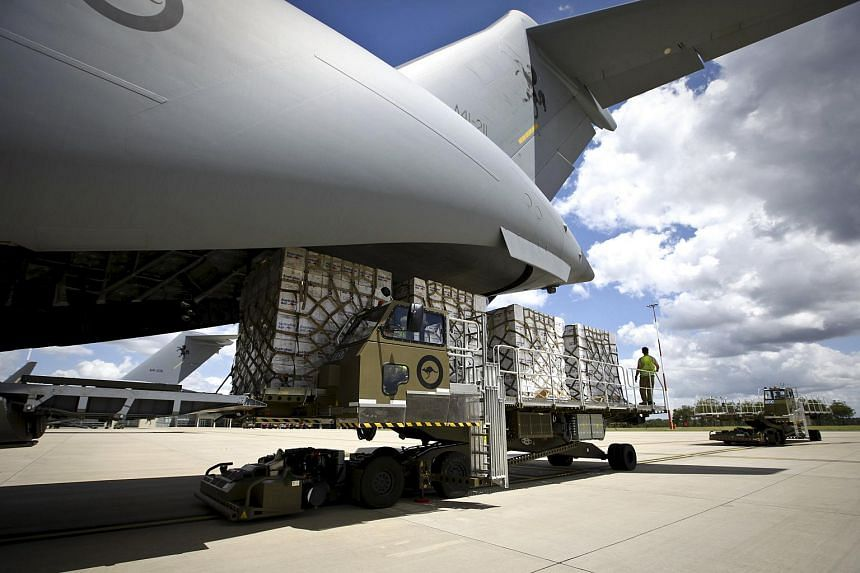 Aid materials are loaded onto an Australian Air Force C-17A aircraft destined for Cyclone Winston-affected Fiji, on Feb 23, 2016.