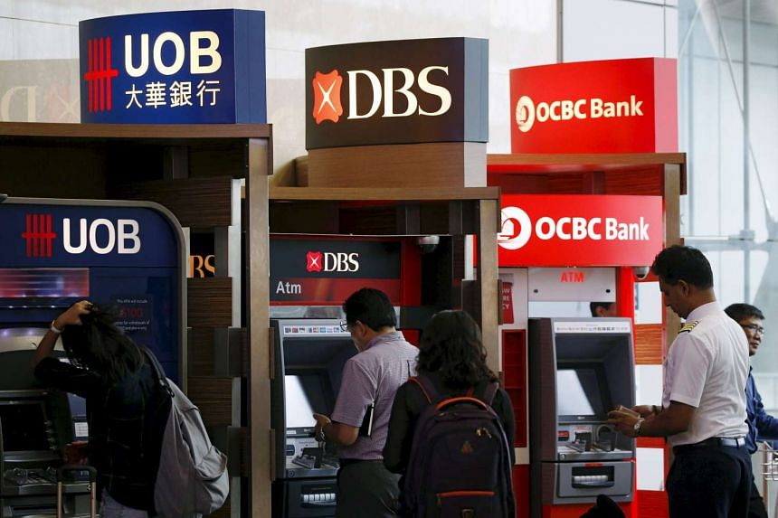 People use automated teller machines of UOB, DBS and OCBC banks in this Jan 5, 2016 file photo.