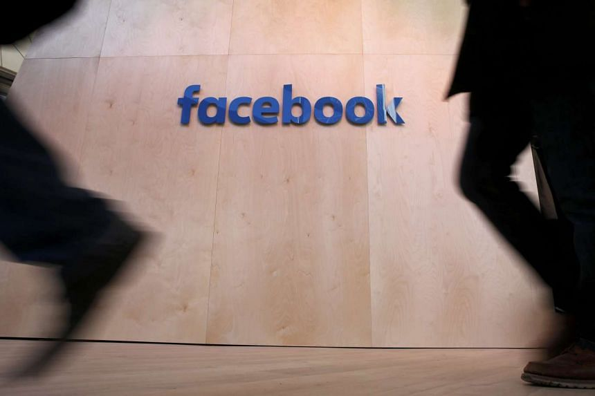 People walk in front of the Facebook logo at the new Facebook Innovation Hub in Berlin, Germany, on Feb 24, 2016.