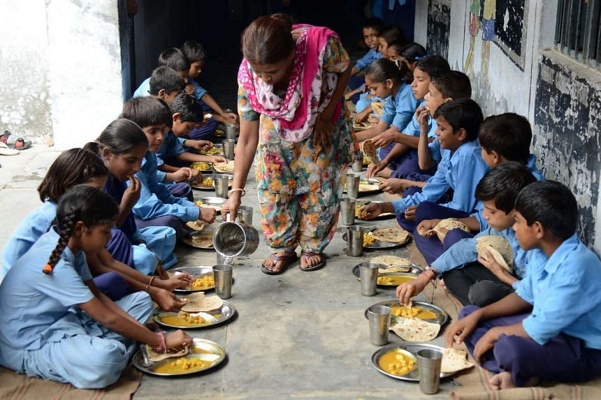 A file picture taken on July 19, 2013, shows Indian schoolchildren eating a free mid-day meal at a government school in Amritsar.