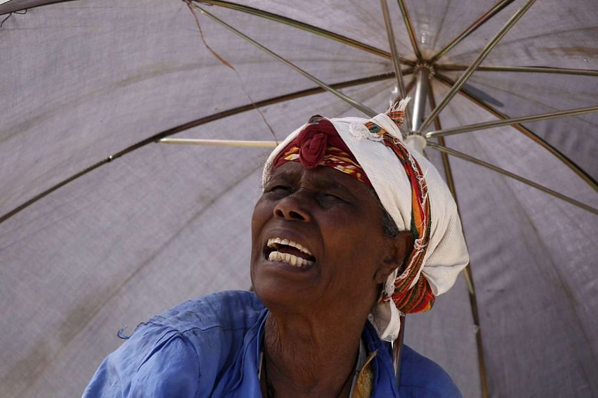 A market stall holder shields herself from the sun in Addis Ababa, Ethiopia, on Nov 28, 2015.
