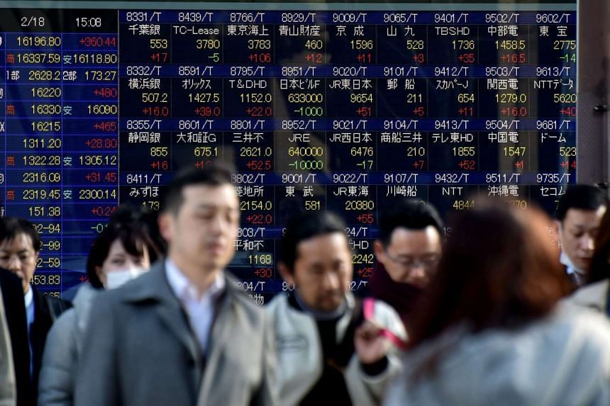 Pedestrians walking past a stock prices board in Tokyo on Feb 18.
