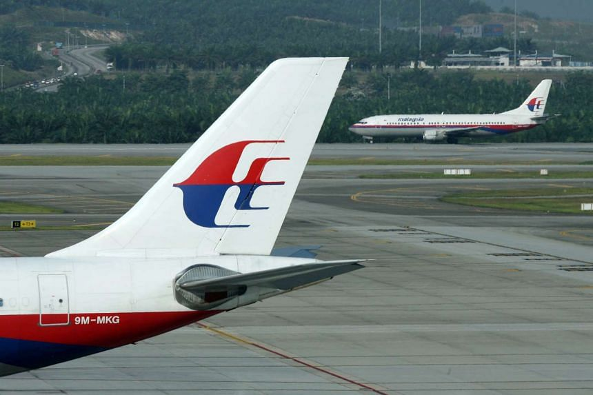 A Malaysian Airlines airplane is parked on the tarmac while another prepares for takeoff, at Kuala Lumpur International Airport.