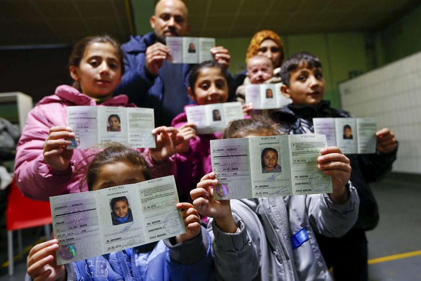 Syrian migrants Wafy Al-Hamoud Alkhaldy, 36, his wife Asma Al Saleh, 33, and their six children presenting their newly issued German registration documents in Herford, western Germany, on Feb 22.