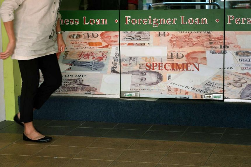 A lady passes by the a moneylending shop in Toa Payoh Central on Nov 4, 2014.