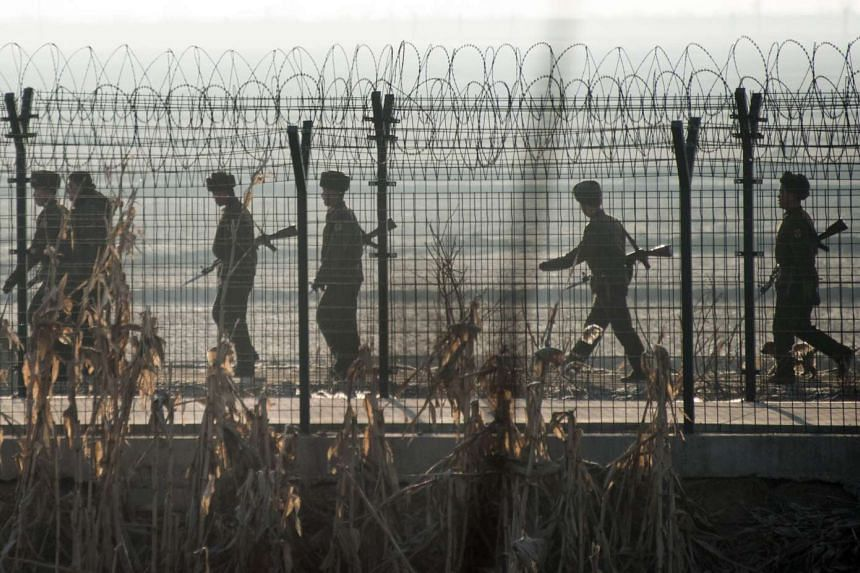 North Korean soldiers patrolling next to the border fence near Sinuiju, across from the Chinese border town of Dandong, on Feb 10, 2016.