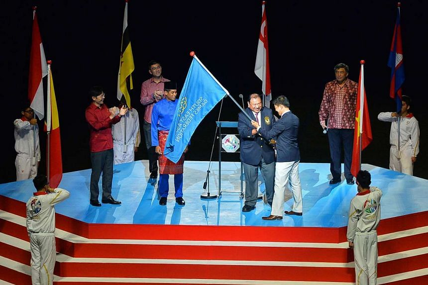 Tunku Imran, president of the Olympic Council of Malaysia, receiving the SEA Games Federation flag from Singapore National Olympic Council president Tan Chuan-Jin at the 28th SEA Games closing ceremony on June 16, 2015.