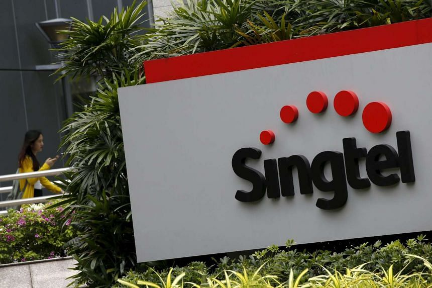 A woman using a mobile phone walks behind a Singtel sign at the head office, on Feb 11, 2016.