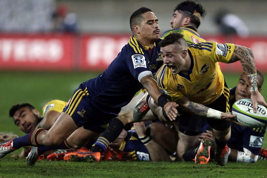 Aaron Smith of the Otago Highlanders tackles the Wellington Hurricanes' T.J. Perenara (right) during last year's Super Rugby final. The Highlanders may face extra pressure as the reigning champions, but both teams are expected to be title contend