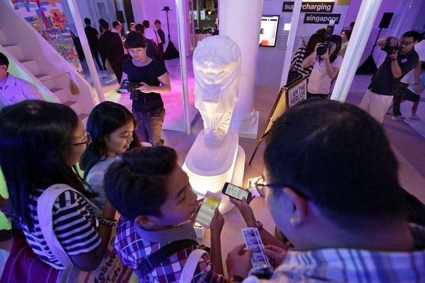 Visitors at the Festival of Tech trying to strike up a conversation with a mini Merlion through mobile texting on Oct 10, 2015.