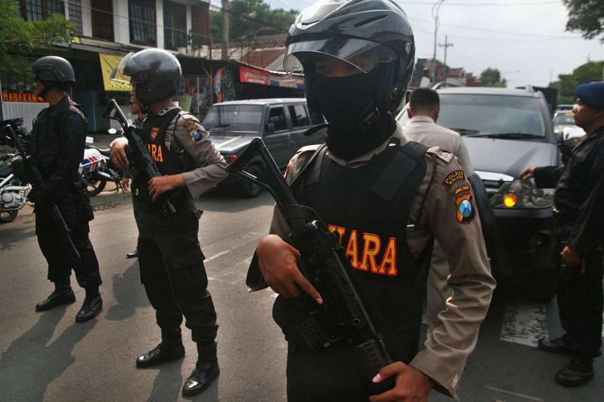 Indonesian police standing guard as an anti-terror squad raids the home of a suspect in Malang, East Java province, on Feb 20.