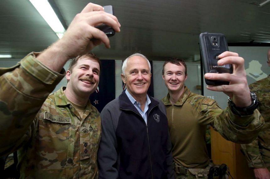 Australian Prime Minister Malcolm Turnbull (centre) posing for photographs with soldiers at the Australian Army base in Camp Taji, Iraq, on Jan 16.