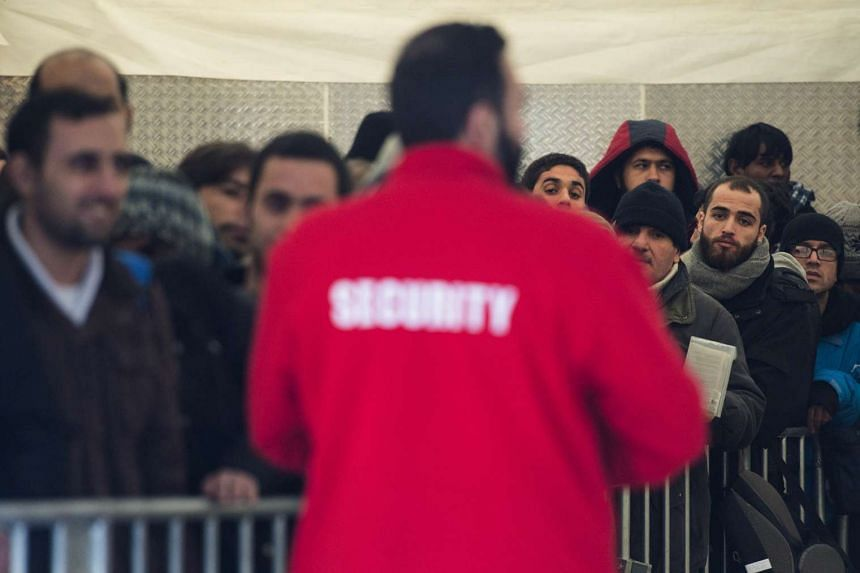 A security officer watches over asylum seekers queuing at a registration centre in Berlin.