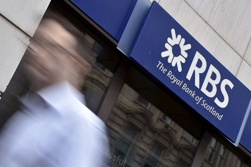 A man walking past a branch of The Royal Bank of Scotland (RBS) in central London.