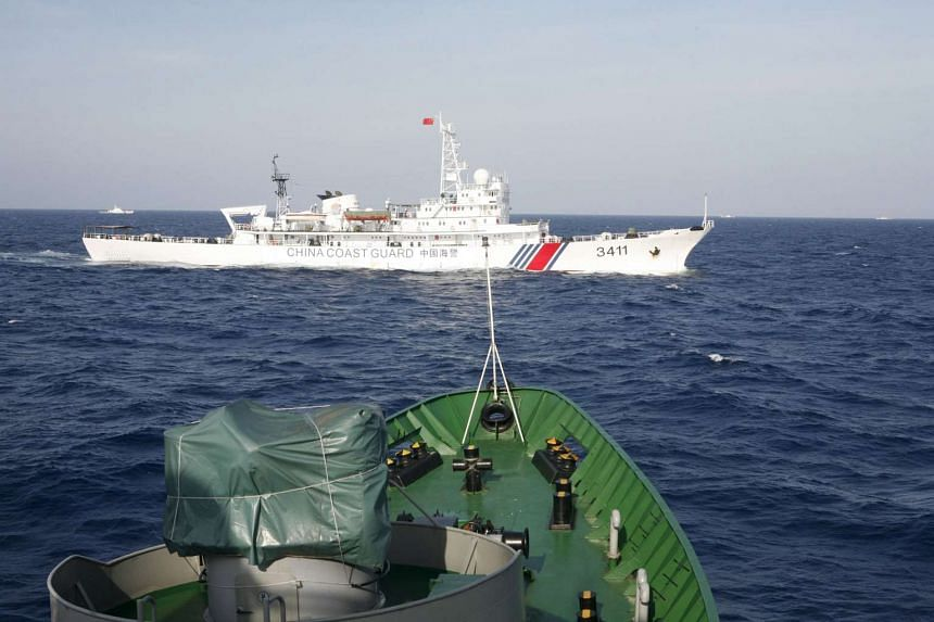 A Chinese Coast Guard ship (top) is seen near a Vietnam Marine Guard ship in the South China Sea.