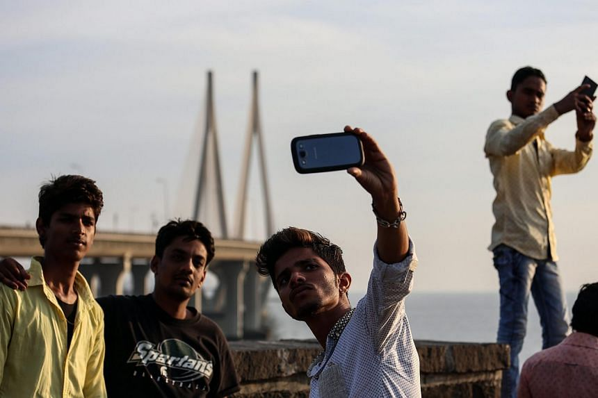 People take selfies at a famous tourist spot near the Arabian sea on Feb 25, 2016.